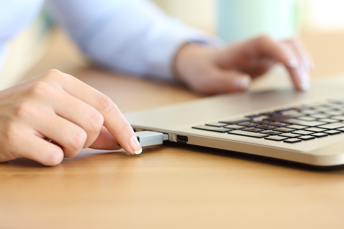 Woman hand connecting a pendrive in a laptop